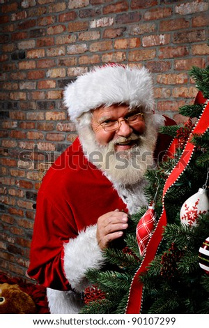 Santa Claus smiling as he is sneaking around the Christmas Tree. - stock photo