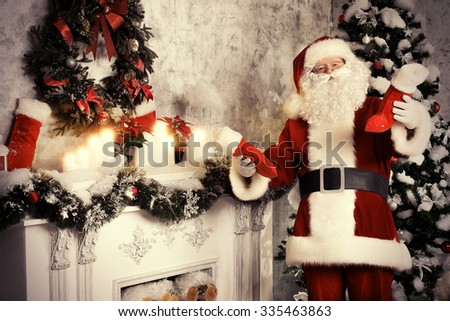 Santa Claus standing by the fireplace and Christmas tree in a beautiful room, decorated for Christmas. He puts Christmas gifts in socks. - stock photo