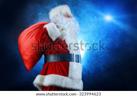 Santa Claus stands with a huge bag of gifts over dark background. Christmas time.  - stock photo