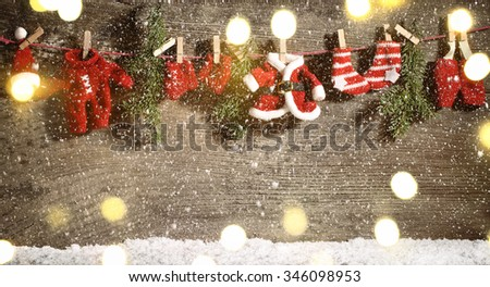 Santa Claus suit hanged on clothes line on wooden background.