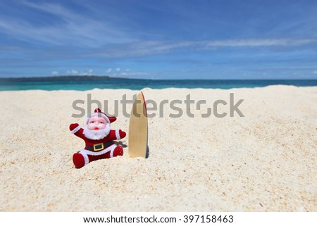 Santa Claus surfer on sand at tropical ocean beach, Christmas and New Year winter vacation concept - stock photo