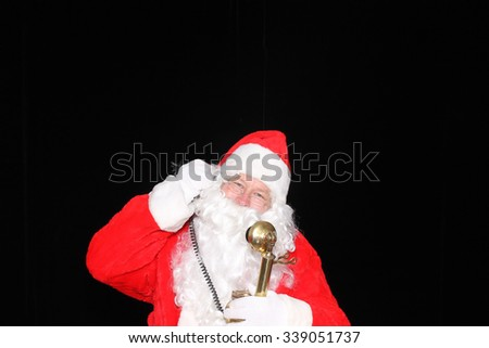 Santa Claus takes orders for Christmas Presents on his Golden Telephone. Santa Phone. Call Santa. Santa Claus hot line. Hello this is Santa. Santa Claus talks on his Phone to people around the world. - stock photo