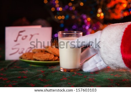 Santa Claus taking milk and cookies offers - stock photo