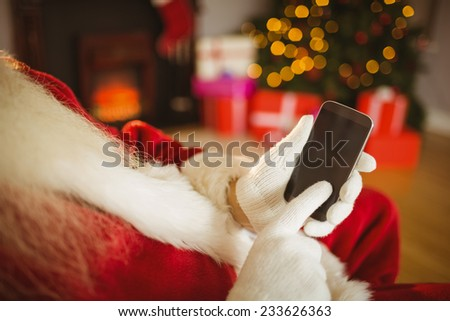 Santa claus touching a smartphone at christmas at home in the living room - stock photo
