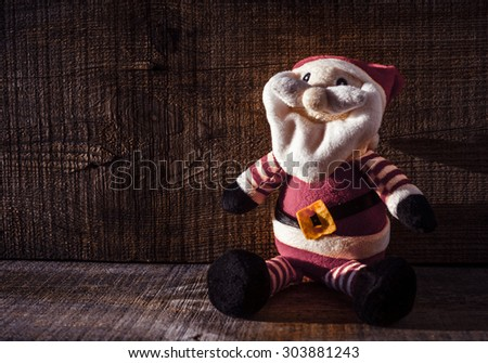 Santa Claus toy against wooden background 