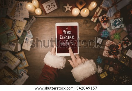 Santa Claus using a digital touch screen tablet, hands close up, top view, desktop with letters and Christmas gifts on background - stock photo