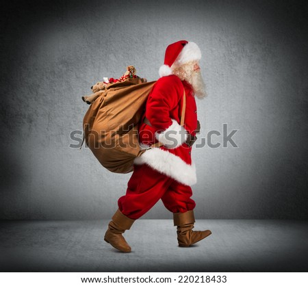 Santa Claus walking with the bag of the presents - stock photo