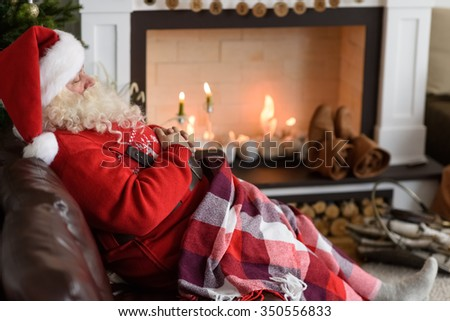 Santa Claus Warming near Fireplace at Home - stock photo