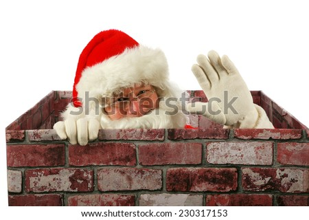 Santa Claus waves at you the viewer while in a Chimney delivering presents to good boys and girls around the world. Santa enters your house through your chimney with the help of his Christmas Magic. - stock photo