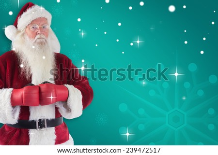 Santa Claus wears boxing gloves against green snowflake background - stock photo