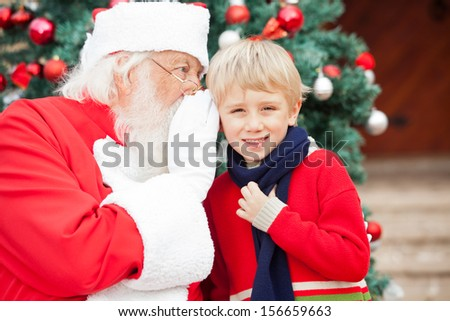 Santa Claus whispering in boy's ear against Christmas tree - stock photo