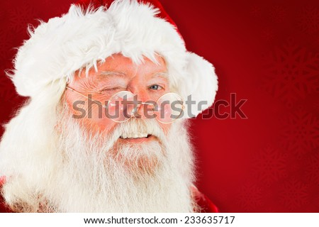 Santa claus winking against red background - stock photo
