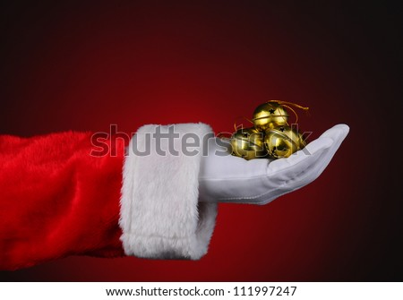 Santa Claus with a handful of gold sleigh bells over a red light to dark background. Horizontal format showing only hand and arm. - stock photo