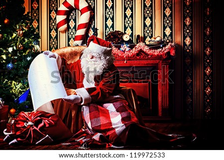 Santa Claus with a list of Christmas presents sitting in a comfortable chair near the fireplace at home. - stock photo