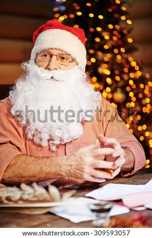Santa Claus with beard wearing shirt and traditional xmas cap - stock photo