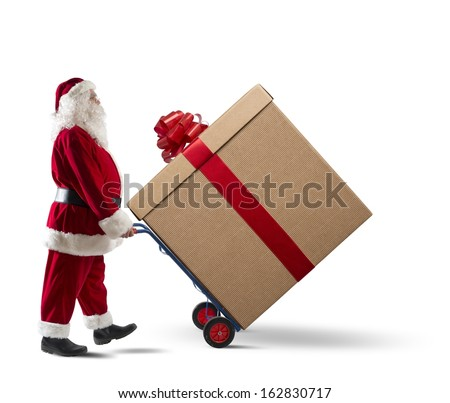 Santa Claus with big Christmas present in a cart - stock photo
