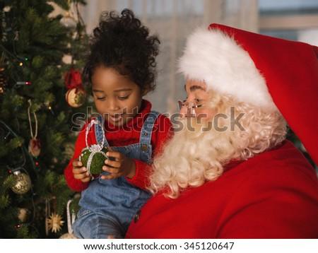 Santa Claus with Child Decorating Christmas Tree - stock photo