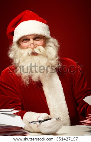 Santa Claus with Christmas letters looking at camera - stock photo