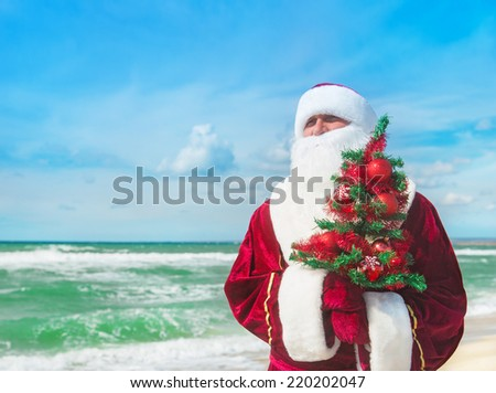 Santa Claus with decorated christmas tree on tropical sea beach - happy new year concept - stock photo