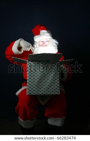 """Santa Claus with Enhanced Blue Eyes opens a box full of """"Christmas Magic"""" and releases it into the world just in time for Christmas - stock photo"""