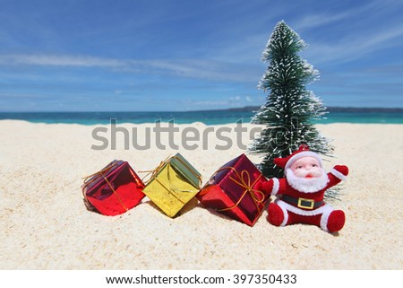 Santa Claus with fir tree and gifts on sand at tropical ocean beach, Christmas and New Year winter vacation concept - stock photo