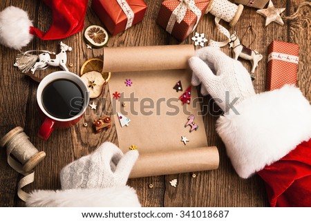 Santa Claus with gifts and wish list on wooden table - stock photo