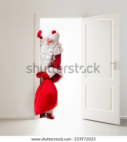 Santa Claus with gifts standing in the doorway. - stock photo