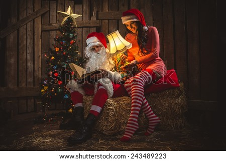 Santa Claus with his sack full of presents and helper woman  - stock photo