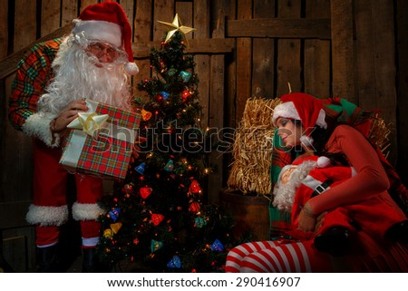 Santa Claus with his sack full of presents and sleeping woman  - stock photo