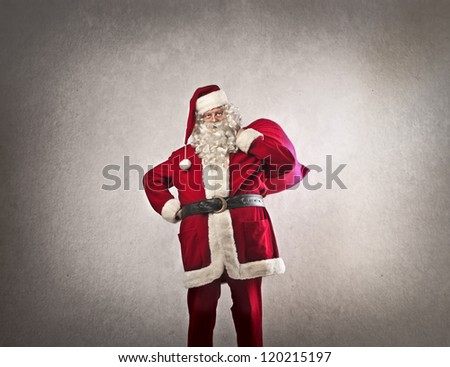Santa Claus with his sack full of presents on a dark white background - stock photo
