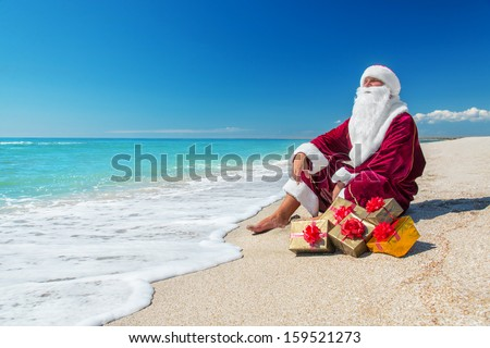 Santa Claus with many golden gifts relaxing on sea beach  - christmas  or happy new year concept - stock photo