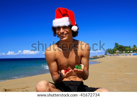 Santa Claus with present boxes on beach - stock photo