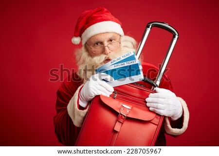 Santa Claus with red leather suitcase and airline tickets in isolation - stock photo