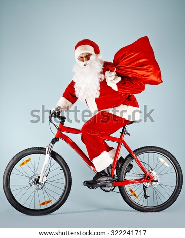 Santa Claus with red sack riding bicycle - stock photo