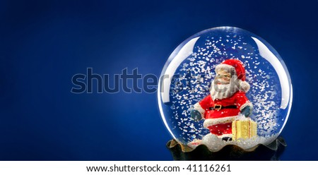 Santa Claus with snow in a sphere - stock photo
