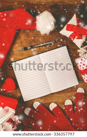 Santa Claus work desk, empty notebook as copy space for good children wish list, hat and gloves with Christmas gifts and presents, top view - stock photo