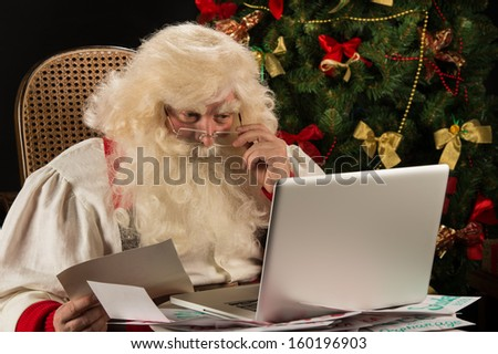 Santa Claus working on computer reading emails and paper letters from children from all over the world - stock photo