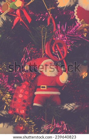 santa clause doll on christmas tree with retro filter effect or instagram filter - stock photo