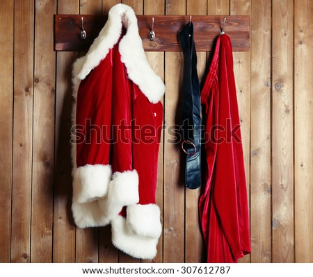 Santa costume hanging on wooden wall background - stock photo