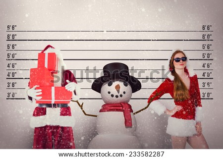 Santa covers his face with presents against mug shot background - stock photo
