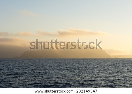 Santa Cruz Island in California??s Channel Islands is engulfed with early morning cloud cover as it is lit by orange sunlight. - stock photo