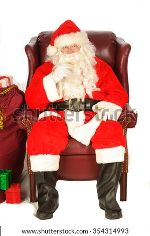 Santa enjoying a rest after a nights work, with a small libation - stock photo