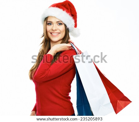 santa girl holding shopping bag. Christmas portrait of young woman with red santa hat. white background isolated. - stock photo