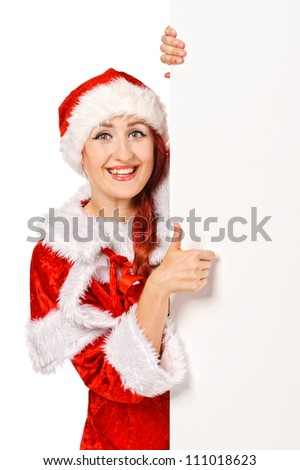 Santa girl peeking from behind blank sign billboard. Caucasian female model isolated on white background - stock photo