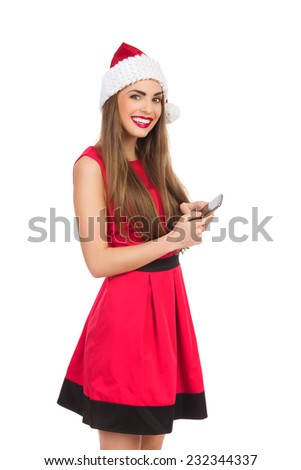 Santa girl sending text message. Beautiful young woman in red santa's hat and dress using a smartphone. Three quarter length studio shot isolated on white. - stock photo