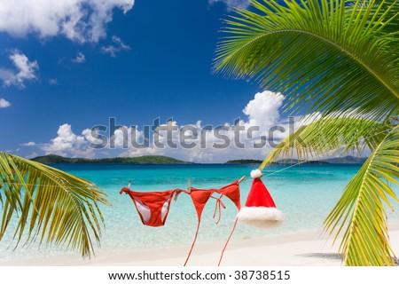 santa hat and bikini hanging on tropical beach - stock photo