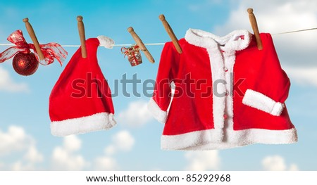 Santa hat and jacket hanging on a clothes line - stock photo