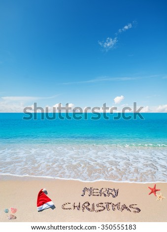 """santa hat and""""merry christmas"""" written on a tropical beach under a blue sky - stock photo"""
