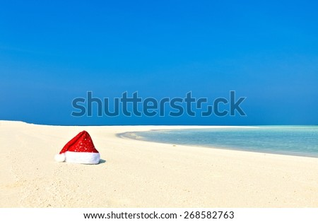 Santa hat is on infinity coral sandy beach (Maldives) - stock photo