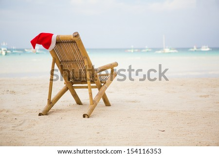 Santa hat on chaise longue on white sand beach - stock photo